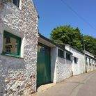 ChelstonCommunityShed, a stone, single-storey building painted white with green doors and window frames