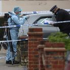A forensic officer at the scene in Tavistock Gardens, Ilford, east London after two men died at a pr