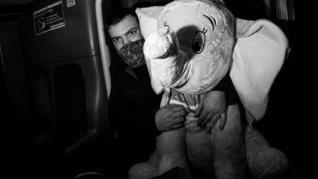 A man holding a cuddly toy on a bus in Ipswich