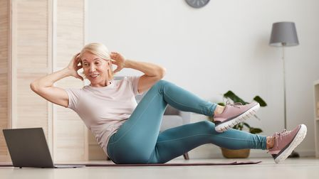 Mature woman sitting on exercise mat and doing exercises during an online session