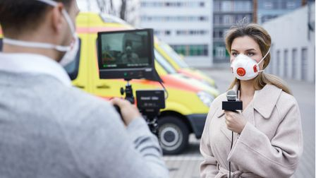 Cameraman and journalist wearing prevention masks. TV news reporters are making reportage about a vi