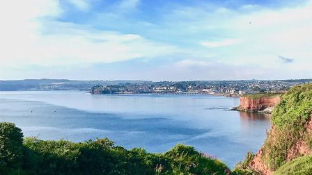 The view of Paignton taken near Livermead, a Azure blue sea and sky with red earth cliffs