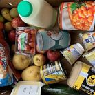 A food hamper with milk, potatoes, tomatoes, eggs, pears