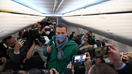 TOPSHOT - Russian opposition leader Alexei Navalny walks to take his seat in a Pobeda airlines plane