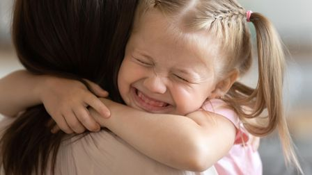 Funny little child girl smiling embrace foster care parent mum, adorable sweet small kid adopted dau