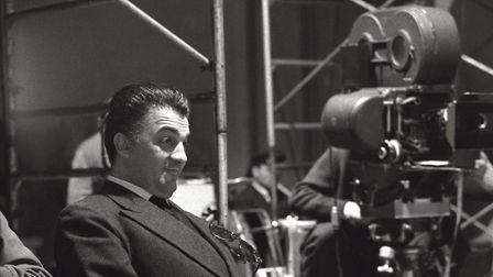 The Italian director Federico Fellini is up near the cinecamera and observes what happens in front o