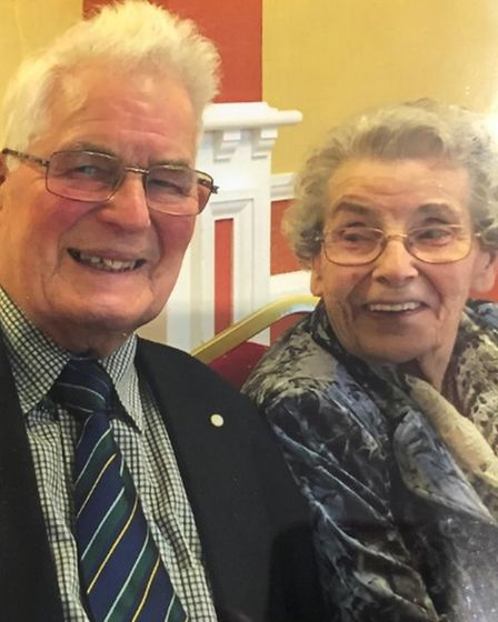 Photo of an elderly couple smiling at the camera