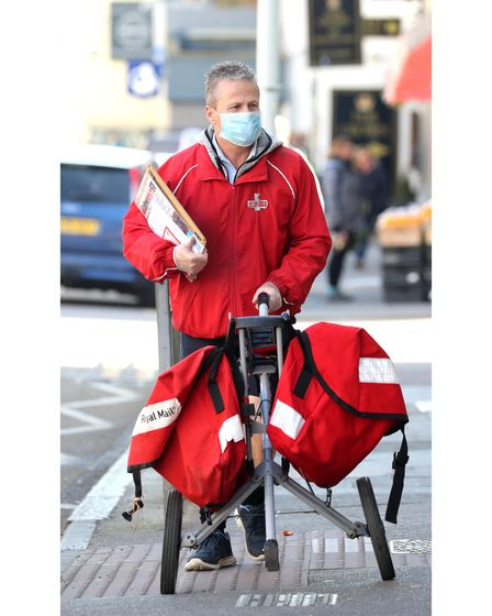 A postman wears a mask and gloves to deliver letters in Broadstairs, Kent, after Prime Minister Bori