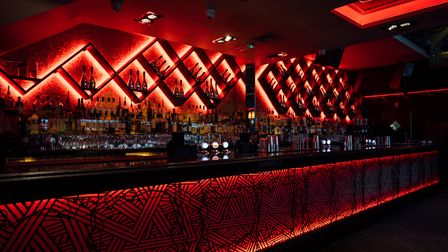 Bar area in a restaurant lit by red strip lights