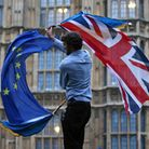 A man waves both a Union flag and a European flag together on College Green outside the Houses of Parliament