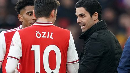 File photo dated 29-12-2019 of Arsenal manager Mikel Arteta (right) speaks to Mesut Ozil from the to