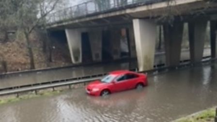 red car stuck in flood water