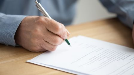 Older male hand signing business document, senior man putting signature on legal paper making invest