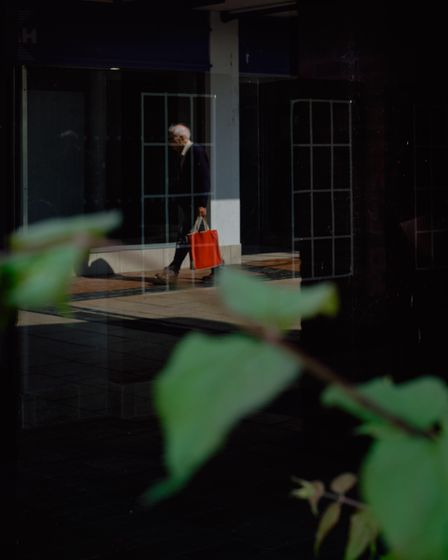 Man in suit carrying red bag reflected in window