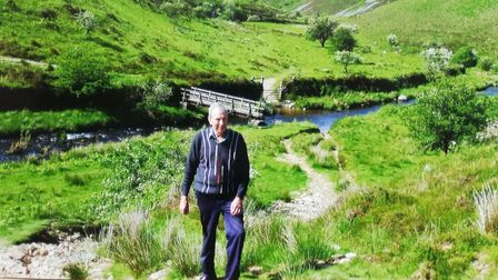 Image of Exmoor Ramble organiser Ivan Huxtable stood in an Exmoor valley with green hills and a stream