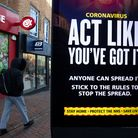 A person passes a 'Act like you've got it' government coronavirus sign on Commercial road in Bournem
