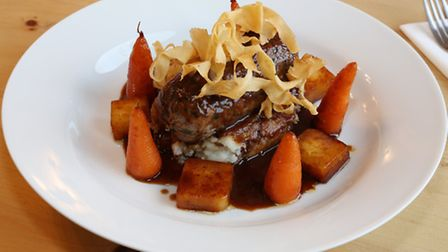 Slow braised lamb shank balloutine, creamy red onion mash, glazed carrots and parsnips with a red cu