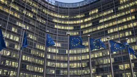 European flags wave in front of the Berlaymont building - European Commission (EC) headquarter - in