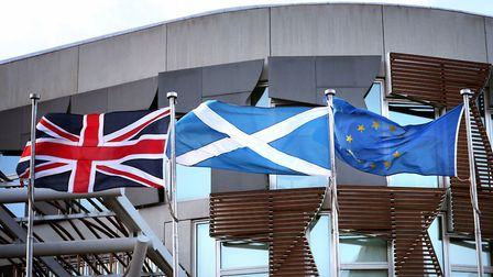 The Union flag, Saltire and the European Union flag fly alongside each other outside the Scottish Pa