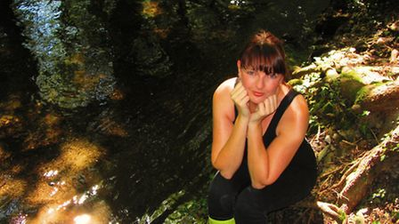 Linzi pictures in a spot in the woods where she gets inspiration