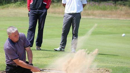 Marc Webb plays from a greenside bunker watched by Stephen Lewis and Luke Taylor