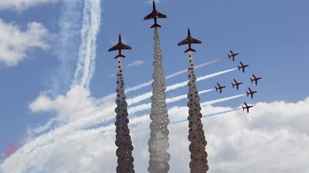 A seven-plane Red Arrows formation fly past the newly unveiled memorial sculpture to their fallen co