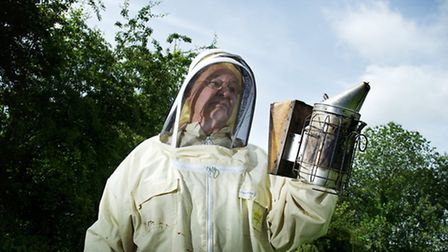 Bob Spruce holding the smoker, ready to inspect his hives