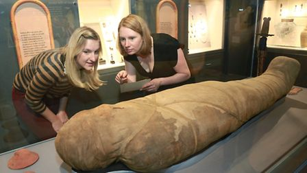 Museum Gallery Officers, Jane Brown and Nicola Euston, inspecting a mummy of NES-AMUN