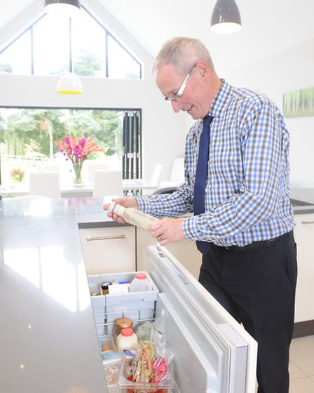 Mike Trower opens the built in refrigerator in his Scandinavian-style home in Ipswich.