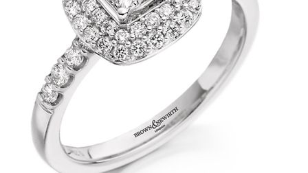 A cluster setting with diamonds on the shoulder. 18ct white gold Princess cut diamond surrounded by