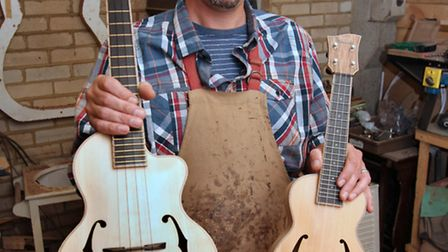 Toby Chennell with one of his latest crafted ukuleles and the first one he ever made, on the right