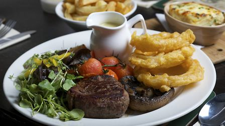 Fillet steak with onion rings and tomatoes. Photo by Mark Bullimore