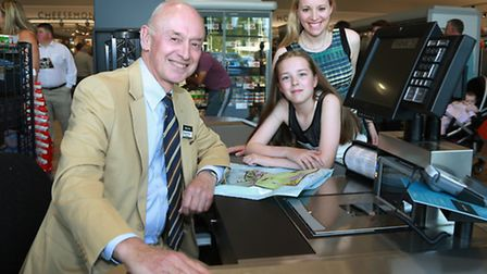 Chairman, Edwin Booth, and Marketing Director, Julie Mills, at the checkout with Ten years old Katie