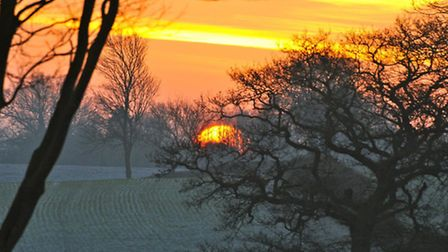 Sunrise taken from the bedroom window of Heather Tanner, over frosty fields at dawn in Mid Suffolk