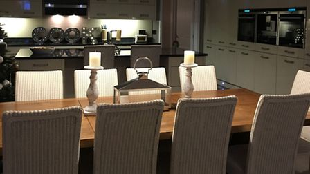 Lighting is repeated along the dining table and echoed in the kitchen with the same shade