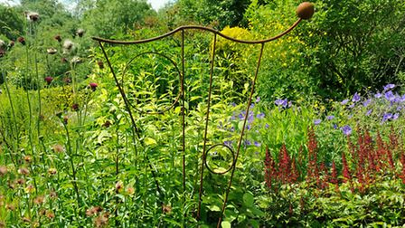 Ian's art-nouveau inspired sculpture in herbaceous bed with Astilbe