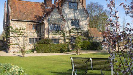 View of Tudor manor house in spring sunshine. Young cherry (Prunus sp.) and various narcissus in the