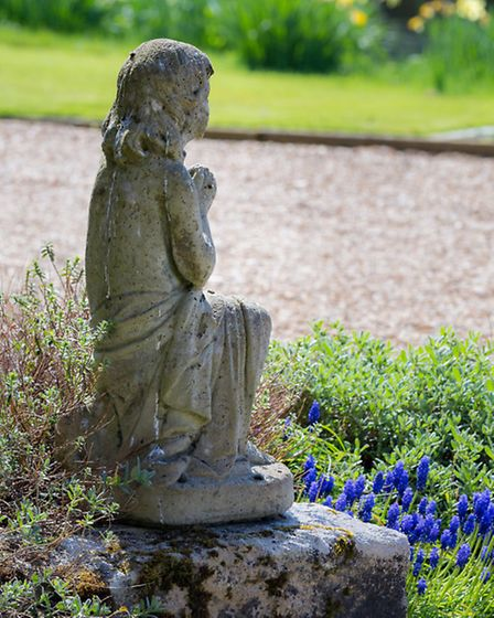 Stone statue of young girl looking out from the front door towards the garden and moat. At her feet