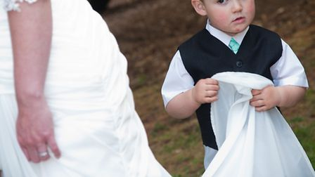 Pictured at the wedding of Jenna and Antony Evans is their son George who is helping his mummy with