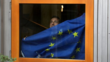 Liberal Democrat MSP Alex Cole Hamilton puts up a European Union flag from his office window after F