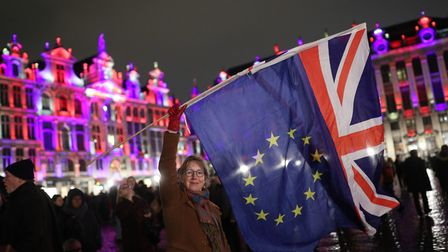 Deirdre Thomas, a resident of Belguim, waving an EU flag and a Union jack in Grand Place in Brussels, Belgium.