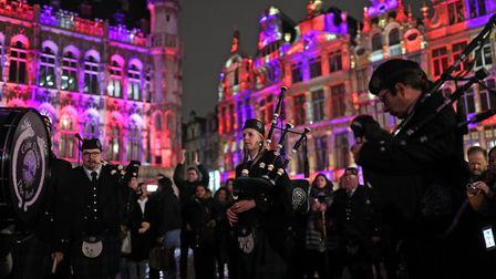 Members of the Celtic Passion Pipe Band playing in Grand Place in Brussels, Belgium, which is lit up