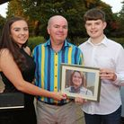 Chris Feeney with children Rosanna and Marcus holding a photograph of mum, Phillipa