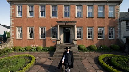 A member of NT staff dressed in costume outside the front of Wordsworth House and Garden, Cockermout