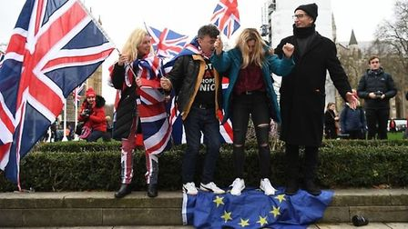 Brexiteers stand on the European flag, ahead of the UK leaving the European Union at 11pm on Friday.