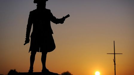 The statue of Captain Vancouver near the Custom House in King's Lynn, watches the setting sun over W