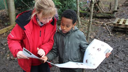 Suzanne examines animal footprints with a learner at Forest School (Picture: Molly Toal)