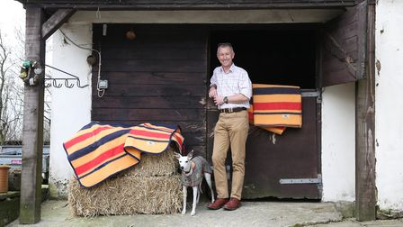 Iain Asher with Tank the dog and a selection of styles of horse blankets