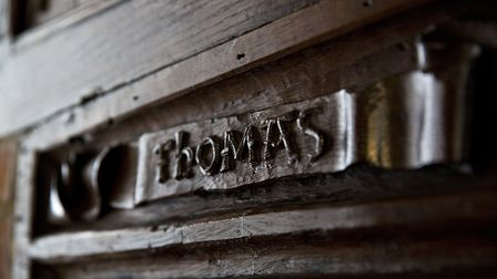 Close up detail of a wooden door plaque reading the name Thomas at Paycocke's House and Garden, Colc