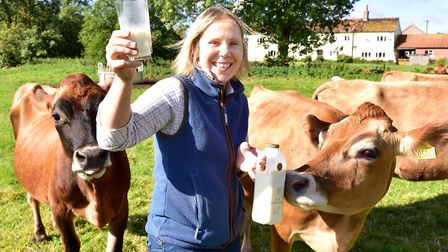 Rebecca Mayhew with the milk and the cows which produce it (photo: Nick Butcher)